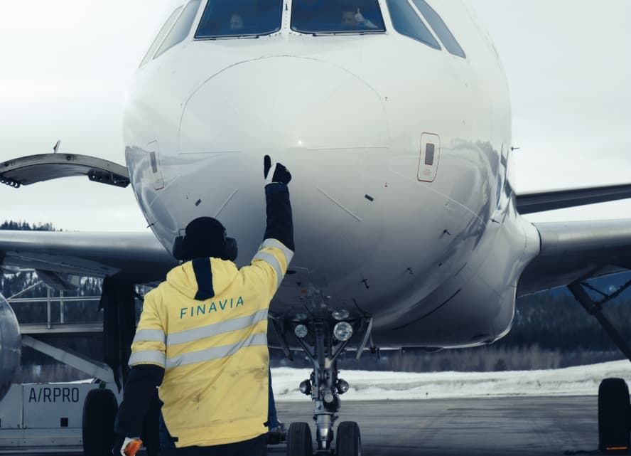 Man marshaling an airplane on Finavia-operated Ivalo airport