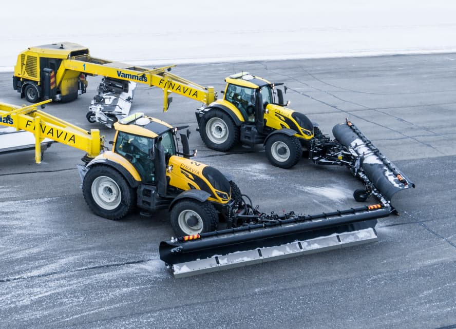 Two snow-plowing Valtra tractors